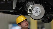 An auto worker checks a vehicle moving along the assembly line at a Geely factory in Cixi, in China's Zhejiang province. Rival Beijing Motor, or BAIC, is launching an IPO in Hong Kong. (CARLOS BARRIA/REUTERS)
