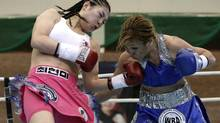 South Korean Champion Choi Hyun Mi, a former North Korean defector, left, lands her punch to Challenger Claudia Andrea Lopez of Argentina during the 9th round of the WBA women's featherweight title match at Sungkyunkwan University in Suwon, South Korea. (Ahn Young-joon.The Associated Press)
