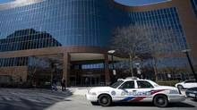 Toronto police stand outside an office building in the city's north end follwoing a stabbing. (NATHAN DENETTE/THE CANADIAN PRESS)