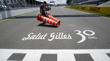 A worker removes cones at the finish line commemorating the anniversary of the death of Canadian driver Gilles Villeneuve at the Canadian Grand Prix, Thursday, June 7, 2012 in Montreal. Villeneuve died 30 years ago during qualifying for the 1982 Belgian Grand Prix at Zolder. (Paul Chiasson/THE CANADIAN PRESS)