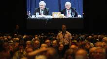 Berkshire Hathaway shareholders listen to CEO Warren Buffett and vice-chairman Charlie Munger seen on a projection screen in the background at the annual meeting in Omaha on May 3. (RICK WILKING/REUTERS)