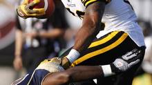 Hamilton Tiger-Cats receiver Onrea Jones is tackled by Winnipeg Blue Bomber David James during second quarter CFL preseason action in Guelph, Ontario Thursday, June 20, 2013. (Aaron Lynett/THE CANADIAN PRESS)