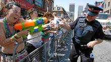 Corinna Gamache fires her water gun at Staff Sergeant Devin Kealey of the Toronto Police Service during the Pride Parade in 2007. (Tibor Kolley/The Globe and Mail)