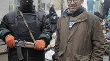 In a photo taken on Sunday, April 13, 2014, reporter Simon Ostrovsky, right, stands next to a pro-Russian militant at a seized police station in the eastern Ukraine town of Slovyansk. (EFREM LUKATSKY/ASSOCIATED PRESS)