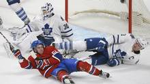 Montreal Canadiens' David Desharnais (51) slides in on Toronto Maple Leafs' goaltender Ben Scrivens and Leafs' Dion Phaneuf (3) during second period NHL hockey action in Montreal, Saturday, Jan. 19, 2013. (Graham Hughes/THE CANADIAN PRESS)