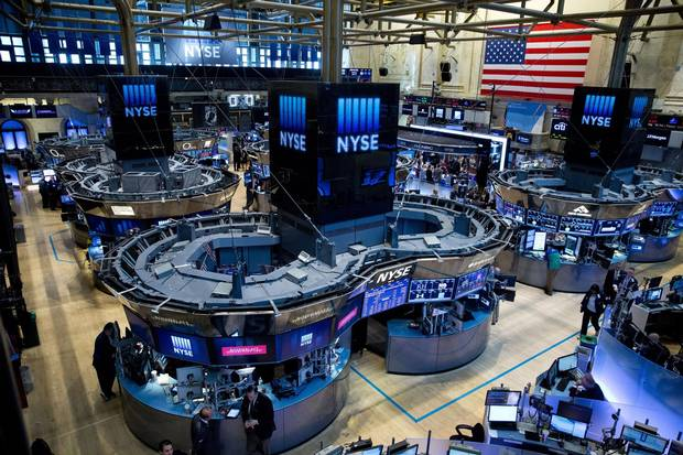 Traders work on the floor of the New York Stock Exchange. U.S. listings have fallen by nearly half over the past 20 years.