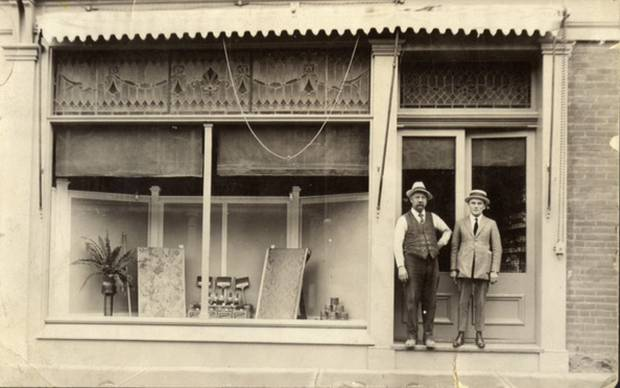 James Harmsworth, left, second generation owner of Harmsworth Decorating Centre, with a company salesman, outside the shop, circa 1920.