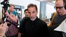 Former New York Rangers head coach John Tortorella, centre, walks out a side door to a waiting vehicle upon arrival at the Vancouver International Airport in Richmond, B.C., on Friday June 21, 2013. Numerous media reports are suggesting he will be named head coach of the Vancouver Canucks. (The Canadian Press)