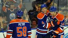 Edmonton Oilers' Jeff Petry, 58, Taylor Hall, 4, and Jordan Eberle, 14, celebrate Hall's second goal of the night during second period NHL pre-season hockey action in Edmonton on Tuesday, September 27, 2011. (Ian Jackson/THE CANADIAN PRESS)