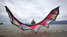 Stephen Codrington, at Spanish Banks Beach in Vancouver on Sunday, lets the air out of the kite he uses when kitesurfing. (DARRYL DYCK For the Globe and Mail)