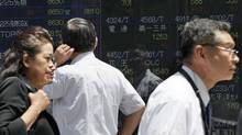 A man checks share prices as others walk by the electronic stock board of a securities firm in Tokyo, June 7, 2012. (Koji Sasahara/AP)