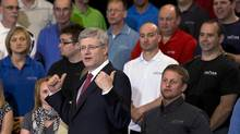 Prime Minister Stephen Harper poses for a group photo with workers at Vector Aerospace in Summerside, Prince Edward Island on Tuesday, May 14, 2013. (Andrew Vaughan/CP)
