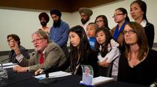 B.C. Federation of Labour President Jim Sinclair, left, is flanked by family members of tragic workplace incidents as he speaks after meeting with Justice Minister Shirley Bond and Labour Minister Margaret MacDiarmid in Vancouver on Tuesday. (DARRYL DYCK/The Canadian Press)