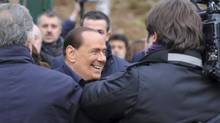 Silvio Berlusconi is surrounded by media as announces in Milan Dec. 8, 2012 that he is running for a fourth term as Italy's prime minister. (Gianni Buzzi, AC Milan press office/AP)