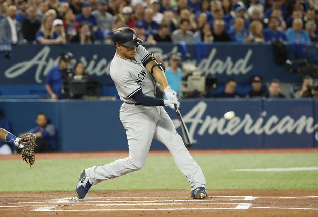 Giancarlo Stanton of the New York Yankees hits a two-run home run against the Toronto Blue Jays in the first inning of the Jays' 2018 home opener.