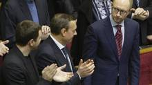 Arseny Yatsenyuk, right, acknowledges applause from his colleagues after being appointed prime minister during a session of the Ukrainian Parliament in Kiev, Thurs. Feb. 27, 2014. He is set to meet Canada's Foreign Affairs Minister John Baird on Friday. (Konstantin Chernichkin/REUTERS)