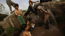 Boys shower in a pool of water created by a broken water pipe on a roadside on the outskirts of Islamabad, Pakistan. (Muhammed Muheisen/AP)