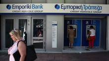 Customers use the ATMs of an Emporiki Bank branch in Athens, Monday, Oct. 1, 2012. (Thanassis Stavrakis/AP)