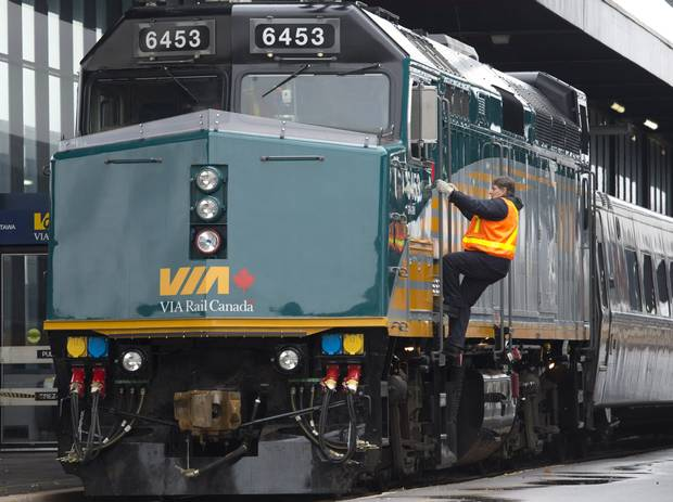 A Via Rail employee climbs aboard an F40 locomotive at the train station in Ottawa on Monday, December 3, 2012. Backbench MPs from the party that gave Canada its first transcontinental railroad appear to be in a losing, behind-the-scenes struggle over cuts at Via Rail, leaving some communities scrambling for new transit options.