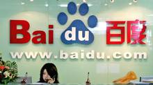 A receptionist works behind the logo for Baidu.com, a Chinese language search engine, at the company's office in Beijing Thursday, July 28, 2005. (NG HAN GUAN/AP)