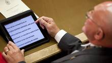Saskatchewan Lieutenant Governor Gordon Barnhart reads the 2010 throne speech from an iPad to open the fall session of the provincial legislature on Wednesday, October 27, 2010 in Regina, Sask. (Troy Fleece/ The Canadian Press/Troy Fleece/ The Canadian Press)
