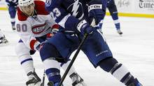 Tampa Bay Lightning's Mike Commodore (R) avoids the check of Montreal Canadiens' Aaron Palushaj during the third period of an NHL game in Tampa, Florida February 28, 2012. (MIKE CARLSON/REUTERS)