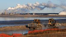 Heavy machinery works in a tailings pond at the Syncrude oil sands plant near Fort McMurray. Criticism of the energy-intensive oil sands has been relentless at the Copenhagen climate summit. Mark Ralston/AFP/Getty Images (MARK RALSTON)