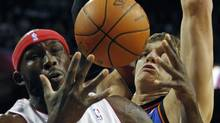 Toronto Raptors' Reggie Evans (L) and New York Knicks' Timofey Mozgov battle for a loose ball during the first half of NBA pre-season action in Montreal, October 22, 2010. REUTERS/Shaun Best (SHAUN BEST)