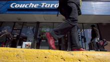 A pedestrian walks past a Couche-Tard convenience store in Montreal, April 18, 2012. (CHRISTINNE MUSCHI/REUTERS)
