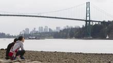 The Lions Gate Bridge can be seen in the background as a couple sit on the beach in West Vancouver, Tuesday, Sept. 13, 2011. (JONATHAN HAYWARD/JONATHAN HAYWARD/THE CANADIAN PRESS)