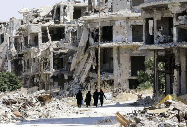 Syrian women walk in between destroyed buildings in the government-held Jouret al-Shiah neighbourhood of the central Syrian city of Homs on Sept.19, 2016.
