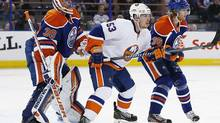 New York Islanders forward Casey Cizikas battles with Edmonton Oilers defensemen Philip Larsen in front of goaltender Ben Scrivens during the third-period action in Edmonton Thursday, March 6, 2014. (Perry Nelson/USA Today Sports)
