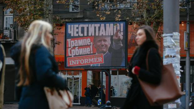 Pedestrians stand by a billboard of U.S. President Donald Trump with the inscription 'Congratulations! Trump Serb!' in Belgrade in November, 2016.