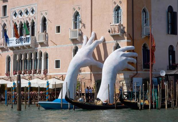 Lorenzo Quinn's work titled, 'Support', features two giant hands reaching out of the Grand Canal in front of the Ca' Sagredo Hotel.