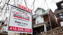 A real estate sign is posted in Toronto's east-end neighbourhood of The Beach on February 25, 2012. (Michelle Siu for The Globe and Mail)