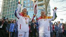 IOC President Thomas Bach, right, hands over the Olympic torch to United Nations Secretary-General Ban Ki-moon as the torch relay arrives in Sochi, ahead of the 2014 Winter Olympics, Thursday, Feb. 6, 2014, in Russia. (Shamil Zhumatov/AP)