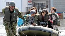 A soldier pulls a rubber boat carrying evacuated people at Ishinomaki city in Miyagi prefecture on March 13, 2011. (Jiji Press/AFP/Getty Images/Jiji Press/AFP/Getty Images)