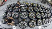 Red Bull technicans mark tires and take notes in the pit-lane ahead of the Abu Dhabi F1 Grand Prix at the Yas Marina circuit in Abu Dhabi on Nov. 10, 2011. (HAMAD I MOHAMMED/Hamad I Mohammad/Reuters)