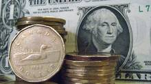 Canadian dollar coins are shown alongside the U.S. dollar. (Ryan Remiorz/Ryan Remiorz/THE CANADIAN PRESS)