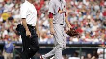 In his final competitive appearance in July, 2008, St. Louis Cardinals starting pitcher Mark Mulder walks off the field, accompanied by a member of the team's medical staff, with discomfort in his left-shoulder. (Tom Mihalek/The Associated Press)