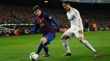 In this Jan. 25, 2012 file photo FC Barcelona's Lionel Messi from Argentina, left, duels for the ball with Real Madrid's Cristiano Ronaldo from Portugal, during their quarterfinal, second leg, Copa del Rey soccer match at the Camp Nou stadium, in Barcelona. (Manu Fernandez/Associated Press)