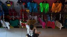 A woman scans racks of clothing at a shopping mall in Beijing July 29. Costs in China have risen so much that Chinese fashion brand Vancl has decided to outsource part of its production. (Andy Wong/AP)
