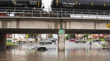 Cars sit in flood water after heavy rainfalls in Regina on June 29, 2014. (LIAM RICHARDS/THE CANADIAN PRESS)