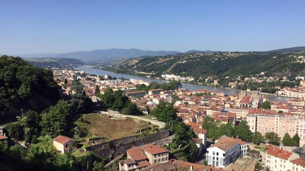 A stop on the river cruise lets travellers view the Rhone behind a town in idyllic Vienne, France.