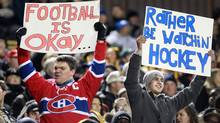 Fans holds signs commenting on the NHL lockout during first half CFL action between the B.C. Lions and Hamilton Tiger-Cats, in Hamilton, Ontario., on Friday, Oct. 12, 2012. (The Canadian Press)