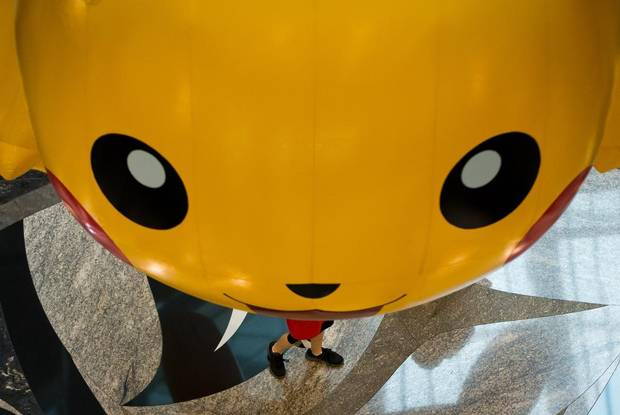 A boy walks under an oversized inflatable of Pokemon character Pikachu hanging at the Vancouver Convention Centre during the 2013 Pokemon World Championships in Vancouver, August 11, 2013.
