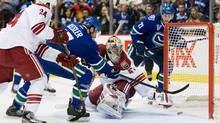 Vancouver Canucks' Ryan Kesler, centre left, scores against Phoenix Coyotes' goalie Mike Smith as Canucks' Mason Raymond, right, and Coyotes Kyle Chipchura, left, watch during the first period of an NHL game in Vancouver, B.C., on Monday April 8, 2013. (DARRYL DYCK/THE CANADIAN PRESS)