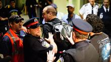 Police remove a person from the area as Air Canada baggage handlers stage a wildcat walkout at Toronto's Pearson International Airport early Friday March 23. (Victor Biro/The Canadian Press/Victor Biro/The Canadian Press)