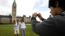 Mexican tourist Borris Frias takes a picture of his travel partners Noe Montano, left, and Erick Ruiz as they visit Parliament Hill in Ottawa on Tuesday July 14, 2009. The Canadian government announced in 2009 that Mexican Nationals will be required to have a visa when visiting Canada. (Sean Kilpatrick/The Canadian Press)