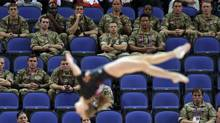 British soldiers watch gymnast Simona Castro Lazo from Chile perform during the Artistic Gymnastics women's qualification at the 2012 Summer Olympics, Sunday, July 29, 2012, in London. Troops, teachers and students are getting free tickets to fill prime seats that were empty at some Olympic venues on the first full day of competition. (Gregory Bull/AP)